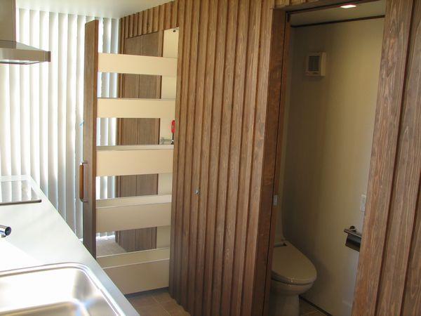 木板壁の奥は、トイレと引き出し式食器収納