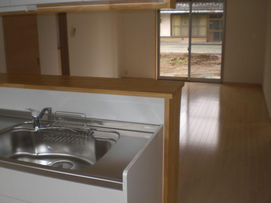 キッチンからLD側を 床の白いフローリングも特徴
